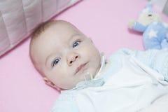 Acorde o bebê de quatro meses que encontra-se no berço com manequim para fora Fotografia de Stock