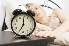 Acorde o tempo: Mulher da Idade Média que alcança para o despertador Fotografia de Stock Royalty Free