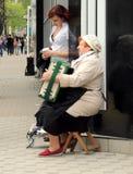 Acordeonista de las mujeres de la calle y su oyente Imagen de archivo