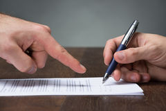 Acordo do sinal de Pointing Partner To do homem de negócios na mesa Fotografia de Stock Royalty Free