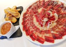 100 Acorn-fed iberico ham. Pata negra. Acorn-fed Iberico Ham. pata negra, ham dish with the fat veining detail next to a cup of crushed tomato and some toasted royalty free stock photos