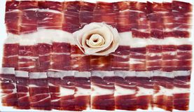 100 Acorn-fed iberico ham. Pata negra. Acorn-fed Iberico Ham. pata negra, top view of a 100% iberico acorn ham dish with a nice flower made with the ham itself royalty free stock photo