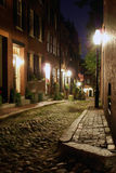 Acorn at night. Sepia toned image of an old 19th Century cobble stone road in Boston Massachusetts, lit only by the gas lamps revealing the shuttered windows and Stock Images