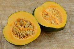 Acorn Squash halves. Raw uncooked acorn squash halves with seeds on burlap Stock Photos