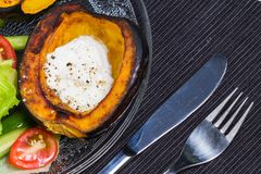 Acorn squash with sour cream and salad. Oven roasted acorn squash, AKA cheastnut squash, with sour cream and black pepper with salad Royalty Free Stock Photography