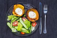 Acorn squash with sour cream and salad. Oven roasted acorn squash, AKA cheastnut squash, with sour cream and black pepper with salad Stock Photo