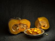 Acorn winter squash, pumpkin, prepared for cooking, cubes with seeds. Life cycle concept. Chiaroscuro, baroque style. Acorn winter squash, pumpkin, prepared for royalty free stock images