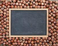 Acorns. Blackboard with acorns on wooden ground Royalty Free Stock Photo