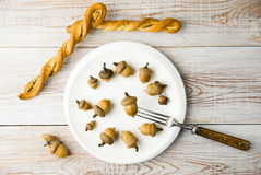 Acorns, plate, fork and bread on the table Royalty Free Stock Images