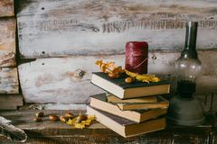 Time to read books. books, candle and oli lamp on the table. woo. Acorns. time to read books. books, candle and oli lamp on the table. wooden background. vintage royalty free stock photos