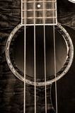 Acoustic Bass Guitar. Close-up of an acoustic bass guitar in sepia tone royalty free stock photography