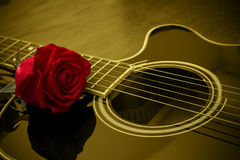 Acoustic black guitar and red rose royalty free stock images