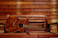 Acoustic brown guitar in wooden stripes Royalty Free Stock Photos