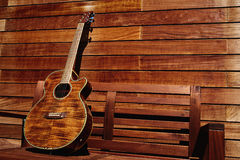 Acoustic brown guitar in wooden stripes Royalty Free Stock Photography