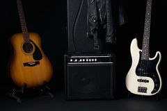 Acoustic country guitar with Black and white electric bass guitar and amplifier Royalty Free Stock Photography