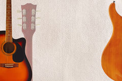 Acoustic and electric guitars and headstock on cardboard background, with plenty of copy space. Acoustic and electric guitars and headstock on the cardboard Stock Photography