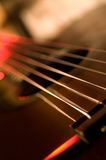Acoustic guitar 02. Fretboard of acoustic guitar. Light background. Lit up red Royalty Free Stock Photography
