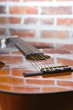Acoustic Guitar. Brown Acoustic Guitar On The Wall Background royalty free stock photos