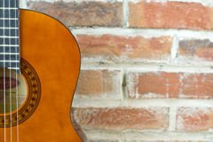 Acoustic Guitar. Brown Acoustic Guitar On The Wall Background royalty free stock photography