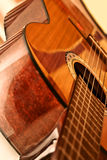 Acoustic Guitar. Polished surface of the body acoustic guitar with a neck and strings Royalty Free Stock Photo