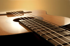 Acoustic guitar. Close and low level angle capturing an acoustic guitar with warm brown background. Focus on foreground strings Stock Image