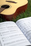 Acoustic Guitar. And music sheet on grass Stock Images