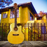 Acoustic Guitar. A yellow spruce top acoustic guitar on a balcony Stock Images