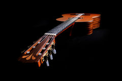 Acoustic guitar. Wooden acoustic guitar lying on side with black background Stock Photo