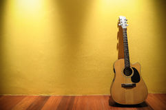 Acoustic guitar. Leaning on yellow wall Stock Images