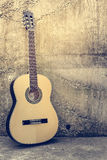 Acoustic Guitar. Against a grunge textured wall Stock Photography