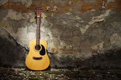 Acoustic guitar against grungy wall. Acoustic guitar leaning on grungy wall Royalty Free Stock Images