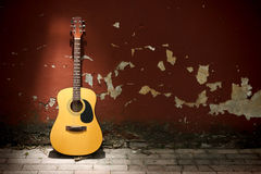 Acoustic guitar against grungy wall. Acoustic guitar leaning on grungy wall Royalty Free Stock Photos