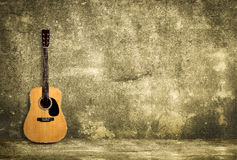 Acoustic guitar against old wall Royalty Free Stock Photo