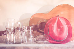 Acoustic guitar and assorted glass bottles on wooden table. Royalty Free Stock Photography