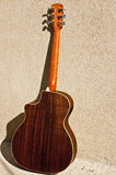 Acoustic Guitar Back Rosewood. An acoustic guitar leaning against a wall showing its back Royalty Free Stock Images