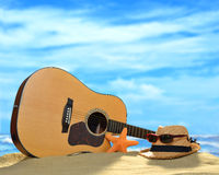 Acoustic guitar on the beach. Acoustic guitar on the sandy beach in summer with blue sea and sky Royalty Free Stock Photos