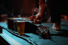 Acoustic guitar and beer on stage at a gig. A musicial adjusts a guitar lying on stage next to a pint of beer at a small gig venue stock photo