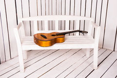 Acoustic guitar on the bench with abstract wooden background Stock Photography