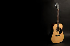 Acoustic guitar on a black background on the right side of the frame, half-turn. Stringed instrument. Horizontal frame. Stock Image