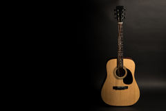 Acoustic guitar on a black background on the right side of the frame. Stringed instrument. Horizontal frame. Stock Image