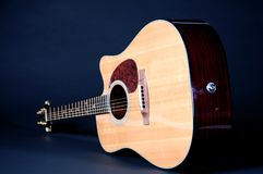 Acoustic Guitar On Black Bk. An acoustic electric guitar isolated against a low key black background in the horizontal format Stock Photography