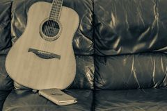 Song writing at home. Acoustic guitar on a black leather couch with leather bound journal Royalty Free Stock Image