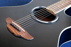 Acoustic guitar with black top with six strings closeup Stock Photography
