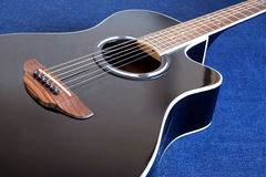 Acoustic guitar with black top with six strings closeup Royalty Free Stock Photos