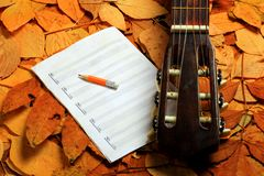 Acoustic guitar, blank music notes, pencil with autumn leaves background. Creative set of acoustic guitar, blank music notes and pencil Stock Images