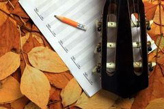 Acoustic guitar, blank music notes, pencil with autumn leaves background. Creative set of acoustic guitar, blank music notes and pencil Royalty Free Stock Image