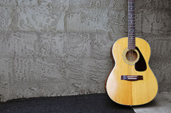 Acoustic Guitar on Block Wall Royalty Free Stock Images