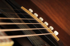 Acoustic Guitar Bridge. Close up photo of a with 6 strings black acoustic guitar bridge Stock Photos