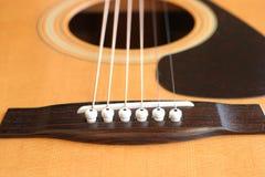 Acoustic Guitar Bridge. The bridge and strings of an acoustic guitar Royalty Free Stock Image
