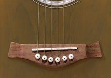Acoustic guitar bridge with saddle, bridge pins and strings Royalty Free Stock Image